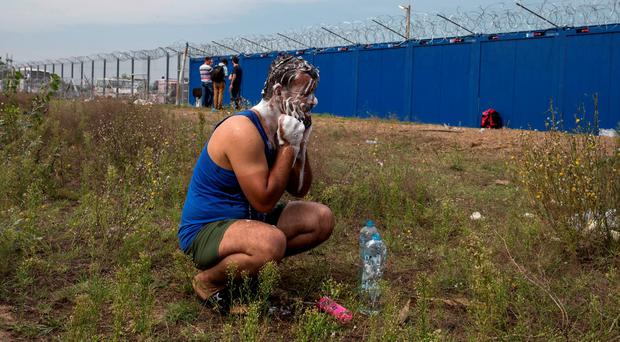 A migrant washes himself in front of a barrier at the border with Hungary near the village of Horgos, Serbia. REUTERS/Marko Djurica