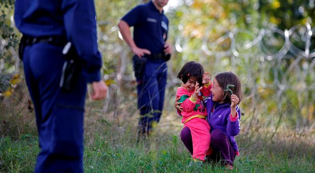 Children guarded by Hungarian police play on the ground after being detained along with other migrants who illegally crossed from Serbia to Hungary near the village of Asotthalom, Hungary. REUTERS/Dado Ruvic