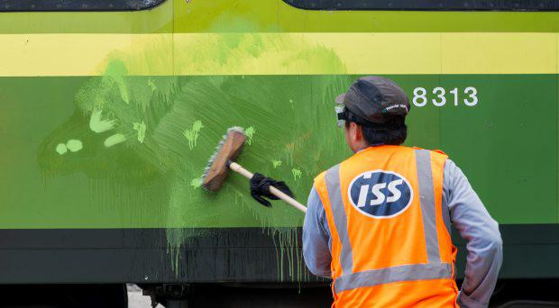 A worker cleaning graffiti from trains