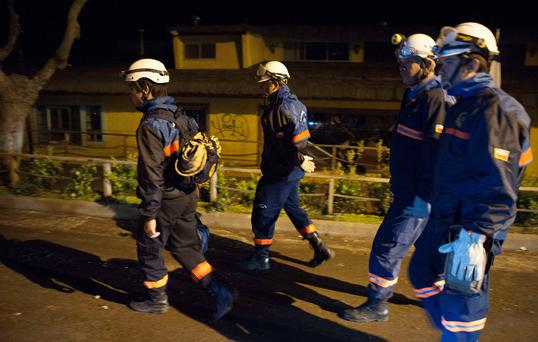 Rescue workers walk through the streets after a large earthquake in Concon, some 110 kms northwest of Santiago on September 16, 2015. Photo: AFP/Getty Images