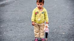 A child holding his doll stands on a road close to a makeshift camp set-up by refugees and migrants on the Serbian side of at the Hungarian border near the town of Horgos, on September 17, 2015, the day after Hungarian riot police fired tear gas and water cannon at crowds of refugees and migrants desperate to cross the border from Serbia, while others carved out a new route and headed for Croatia. AFP PHOTO / ARMEND NIMANIARMEND NIMANI/AFP/Getty Images