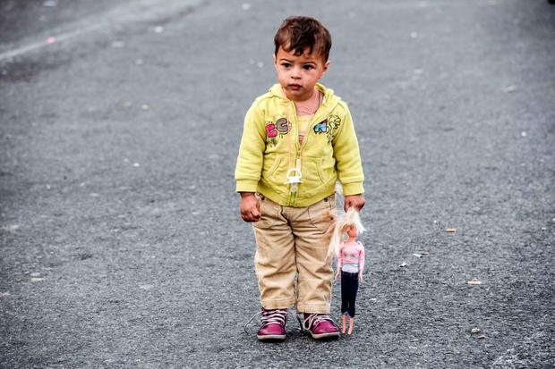 TOPSHOTS A child holding his doll stands on a road close to a makeshift camp set-up by refugees and migrants on the Serbian side of at the Hungarian border near the town of Horgos, on September 17, 2015, the day after Hungarian riot police fired tear gas and water cannon at crowds of refugees and migrants desperate to cross the border from Serbia, while others carved out a new route and headed for Croatia. AFP PHOTO / ARMEND NIMANIARMEND NIMANI/AFP/Getty Images