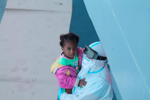 A young girl is held by a crew member of the LÉ Niamh Credit: Irish Defence Forces