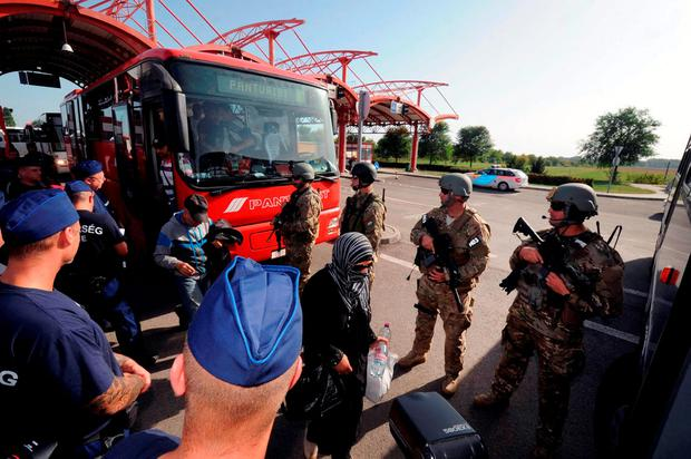 Hungarian soldiers and police stand guard as migrants get off a bus in Beremend near the Hungarian-Croatian border Credit: LASZLO LAUFER (Getty Images)