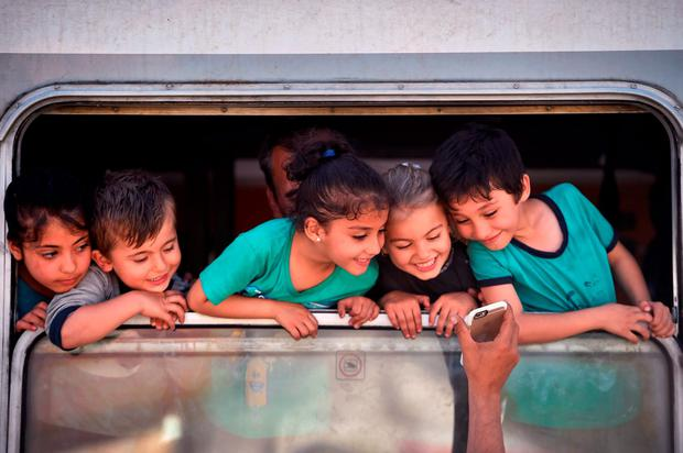 Young children smile a they look at a mobile phone as migrants board trains and buses in Croatia bound for Hungary Credit: Jeff J Mitchell (Getty Images))