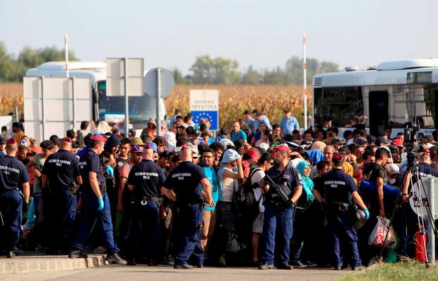 Hungarian policemen direct migrants as they change buses after they crossed the border from Croatia Credit: Bernadett Szabo