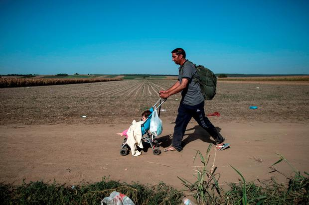 A migrant wheels his child in a pushchair on a dirt road towards the border between Croatia and Serbia. Croatia has fenced off its own border with Serbia after more than 14,000 entered the country Credit: ANDREJ ISAKOVIC