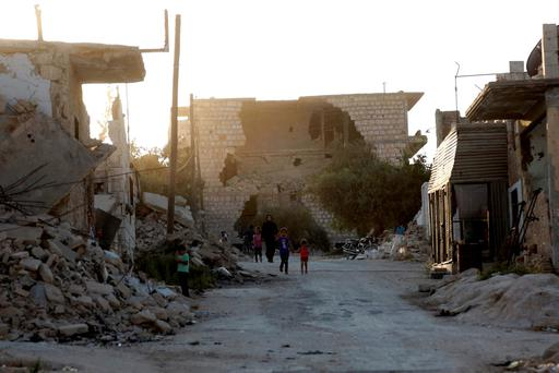 Residents walk near damaged buildings in Maarat Al-Nouman, south of Idlib, Syria REUTERS/Khalil Ashawi?€?