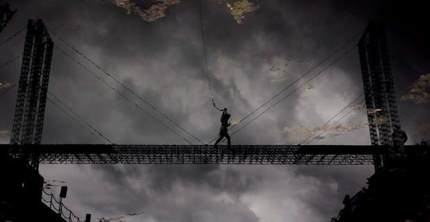 A reflection of Queens Student Claire Hughes as she crosses a Guinness world record breaking Meccano Bridge, spanning more than 100 feet across Clarendon dock in Belfast. Photo: Niall Carson/PA Wire