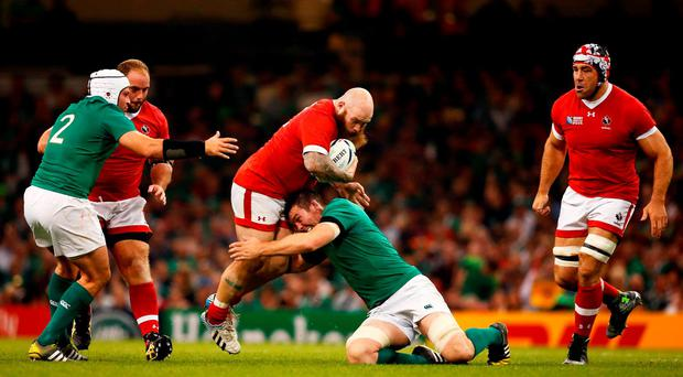 Ray Barkwill of Canada is tackled by stand out performer Iain Henderson of Ireland