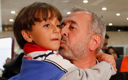 'A DREAM COME TRUE': Osama Abdul Mohsen, a Syrian refugee who was filmed being tripped up by a camerawoman as he fled police in Hungary with his young son, kisses his son Zaid upon their arrival at Barcelona's Sants train station