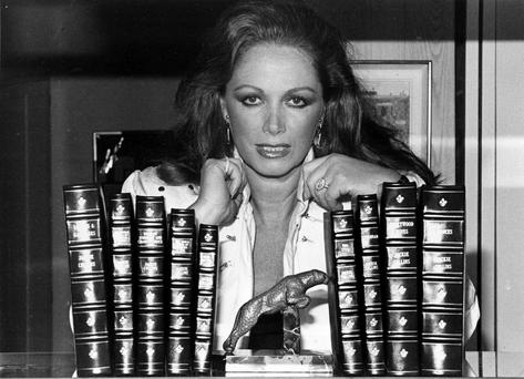 In this July 19, 1984 file photo, author Jackie Collins poses with her books at her home in Beverly Hills, Calif. Collins, died in Los Angeles on Saturday, Sept. 19, 2015, of breast cancer. She was 77. (AP Photo, File)