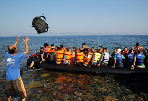 Syrian refugees in a overcrowded dinghy arrive on the Greek island of Lesbos after crossing a part of the Aegean Sea from the Turkish coast (seen in the background) September 20, 2015. Reuters/Yannis Behrakis