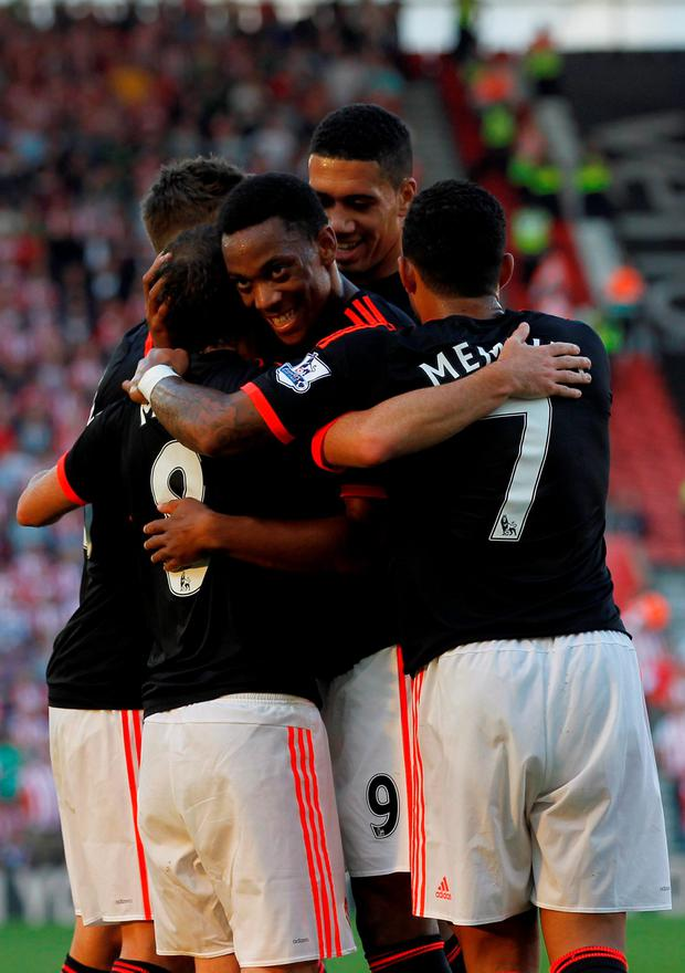 Manchester United's French striker Anthony Martial (C) and teammates congratulate Manchester United's Spanish midfielder Juan Mata (L) on scoring their third goal during the English Premier League football match between Southampton and Manchester United at St Mary's Stadium in Southampton, southern England on September 20, 2015. AFP PHOTO / IAN KINGTON RESTRICTED TO EDITORIAL USE. No use with unauthorized audio, video, data, fixture lists, club/league logos or 'live' services. Online in-match use limited to 75 images, no video emulation. No use in betting, games or single club/league/player publications.IAN KINGTON/AFP/Getty Images