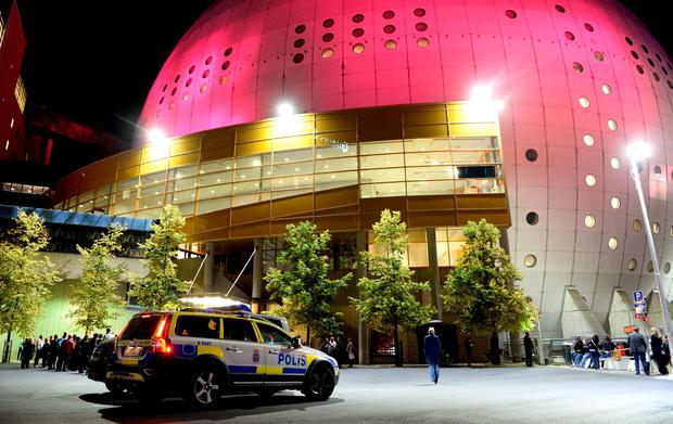 Police and concertgoers wait outside the venue for a U2 concert at the Ericsson Globe Arena in Stockholm, Sweden