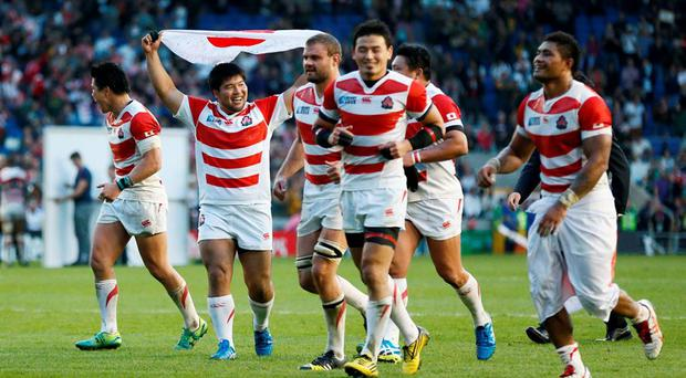 Japan celebrate victory over South Africa Reuters / Stefan Wermuth