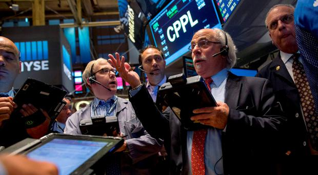 Traders gather at the post that trades Cablevision on the floor of the New York Stock Exchange. Photo: Reuters