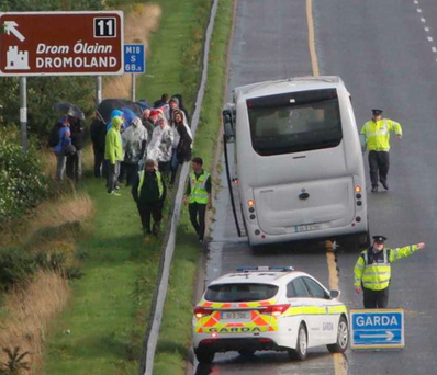 Gardai direct traffic away from a tourist bus after the rear wheels became detached from it