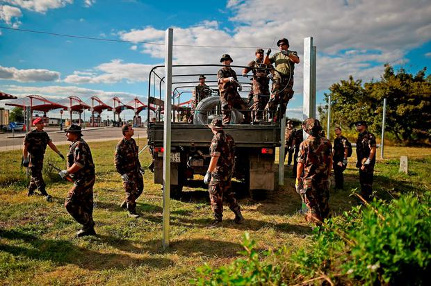 Hungarian soldiers erect a fence at a border point between Croatia and Hungary where migrants are being transported by bus through to Austria Credit: Jeff J Mitchell (Getty Images)
