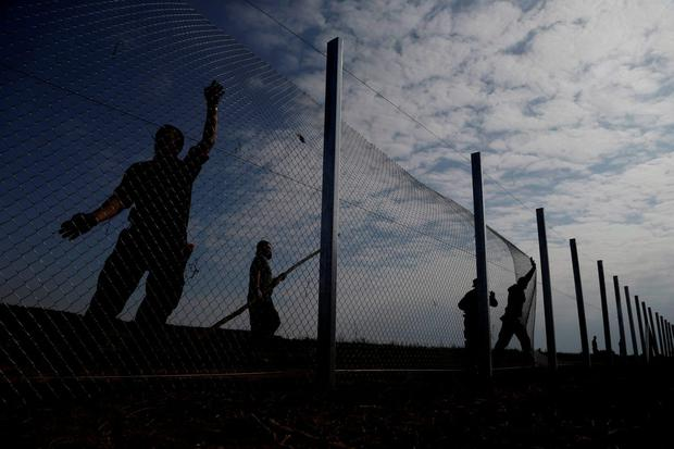 Hungarian soldiers work on a fence at the border with Croatia near the village of Beremend Credit: Petr David Josek (AP)