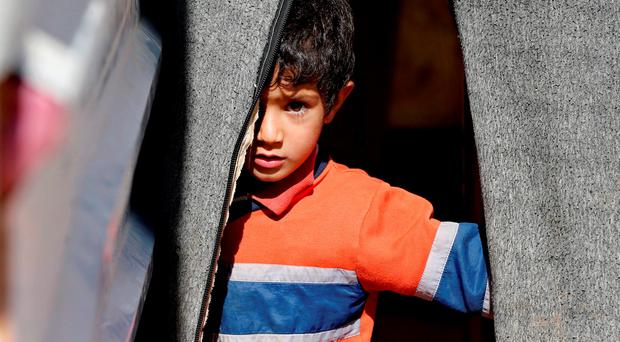 A Syrian refugee boy stands in front of his family's tent in Al Zaatari refugee camp, in the Jordanian city of Mafraq, near the border with Syria, September 22, 2015. REUTERS/ Muhammad Hamed