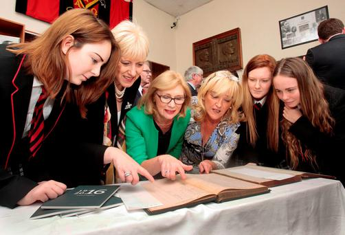 Education Minister Jan O'Sullivan and Arts Minister Heather Humphreys viewing roll books from 1891 with the names of pupils Padraig and Willie Pearse at CBS Westland Row. Also pictured are principal Kate Byrne and pupils Chloe Ellison, Jabe Kelly and Abby Kelly at the launch the Ireland 2016 Schools Programme at the Pearse brothers' former school yesterday Photo: Tom Burke