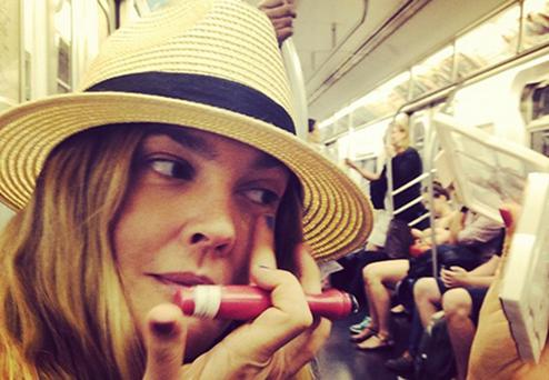 Drew Barrymore applying makeup on the subway