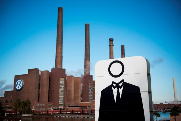 A giant poster with a faceless man is seen next to the headquarters of German car maker Volkswagen in Wolfsburg, central Germany Credit: ODD ANDERSEN