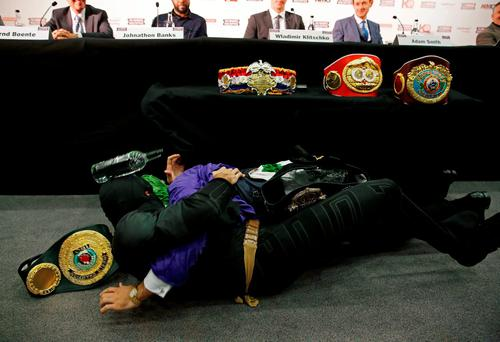 Tyson Fury, dressed as Batman tussles with someone dressed as The Joker during the press conference