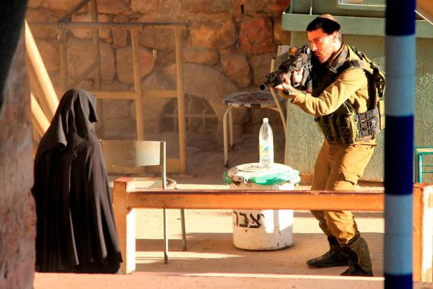 In this photo made available by the Youth Against Settlements, a Palestinian activist network that opposes Jewish settlements in the West Bank, an Israeli soldier aims at a Palestinian woman at a checkpoint in the West Bank city of Hebron.