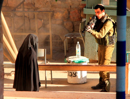 An Israeli soldier aims his rifle at a woman said to be 19-year-old Palestinian student Hadeel al-Hashlamun, before she was shot and killed by Israeli troops