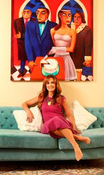 Lorraine with one of her favourite paintings by artist Graham Knuttel. She loves the light and space in her hallway, and chose this turquoise sofa to offer a bright twist between contemporary and traditional design that wouldn't take away from the artwork. Photo: Gerry Mooney.