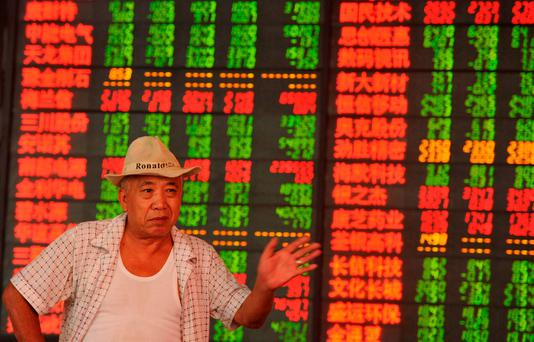 An investor gestures in front of an electronic board showing stock information at a brokerage house, in Fuyang, Anhui province. Photo: Reuters