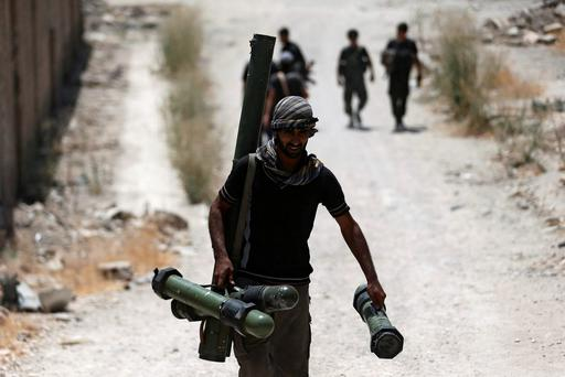 A fighter from the Free Syrian Army's Al Rahman legion carries a weapon as he walks towards his position on the front line against the forces of Syria's President Bashar al-Assad in Jobar, a suburb of Damascus, Syria. Photo: Reuters