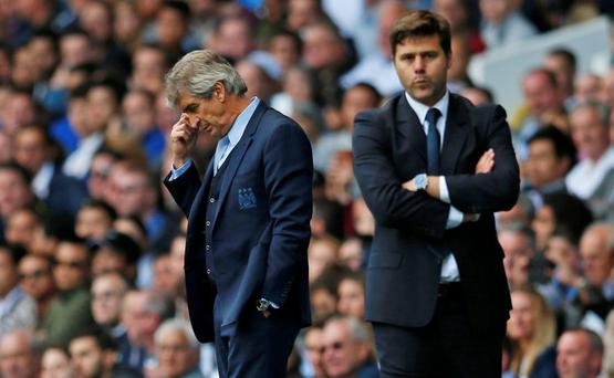 Manchester City manager Manuel Pellegrini looks dejected as Tottenham manager Mauricio Pochettino looks on