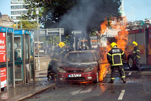 Members of the Dublin Fire Brigade tacklefire in a burning car on Burgh Quay today. Photo: Tony Gavin