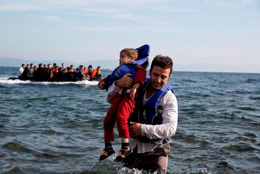 A Syrian refugee carries his child after they arrived from Turkey to the shores of the Greek island of Lesbos
