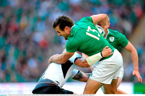 Jared Payne, Ireland, is tackled by Romania's Valentin Calafeteanu,