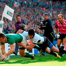 Tommy Bowe goes over to in the corner for his side's first try despite the tackle of Ionut Botezatu