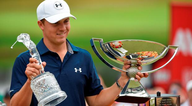 Jordan Spieth holds up his trophies after winning the final round of the Tour Championship at East Lake Golf Club