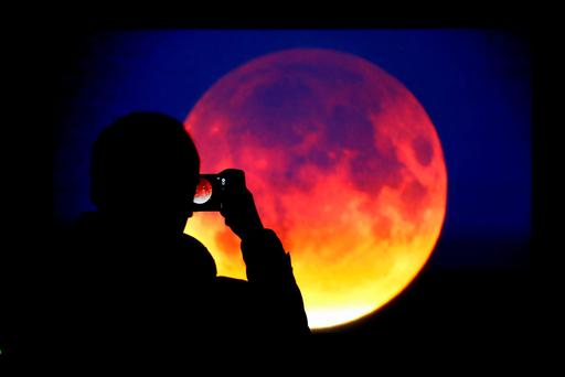 A man takes picture of the screen displaying the moon, appearing in a dim red colour, which is covered by the Earth's shadow during a total lunar eclipse in Warsaw