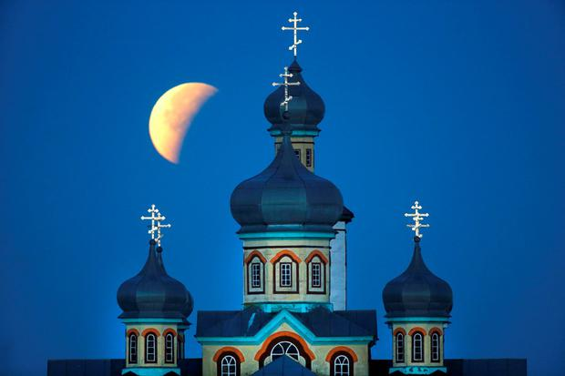 A so-called supermoon is seen at the finish of a lunar eclipse behind an Orthodox church in Turets, Belarus, 110 kilometers (69 miles) west of capital Minsk