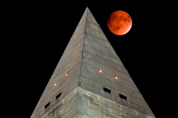 The so-called supermoon passes behind the peak of the Washington Monument during a lunar eclipse