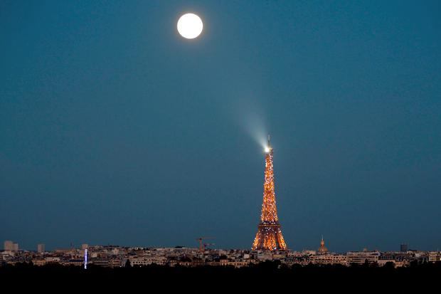 A super moon rises in the sky near the Eiffel tower as seen from Suresnes