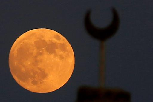 A supermoon, the last of this year's supermoons, rises near the minaret of a mosque in Wadi El-Rayan Lake at the desert of Al Fayoum Governorate, southwest of Cairo