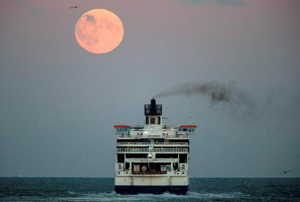 The moon is seen above a cross channel ferry leaving the port of Dover