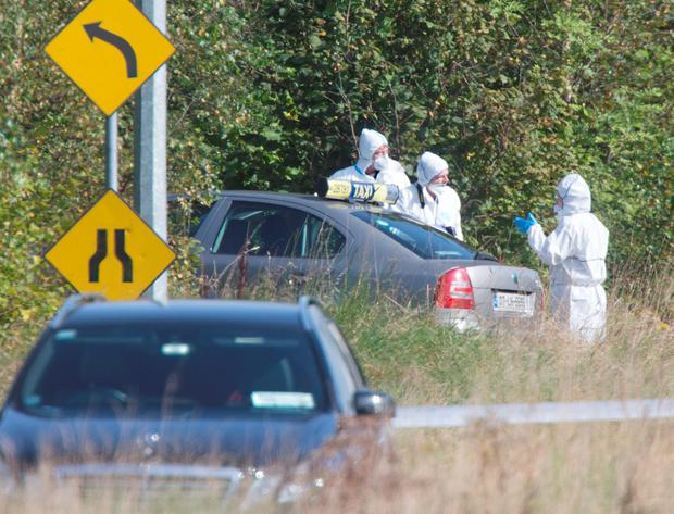 Garda Crime Scene Investigators inspect Mr Mulligan's taxi at the scene of the incident