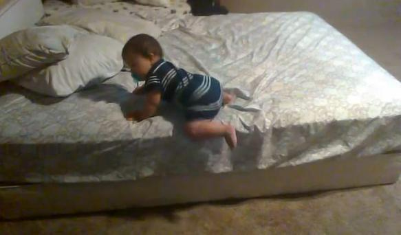 Baby uses problem solving skills to make his way off the bed by himself.