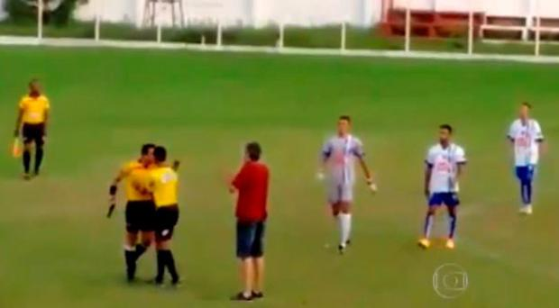 Linesman restraining Gabriel Murta as he holds the gun in his hand Credit: YouTube