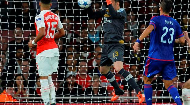 Arsenal's Colombian goalkeeper David Ospina (C) drops the ball over the line from a corner taken by Olympiakos's Greek midfielder Kostas Fortounis